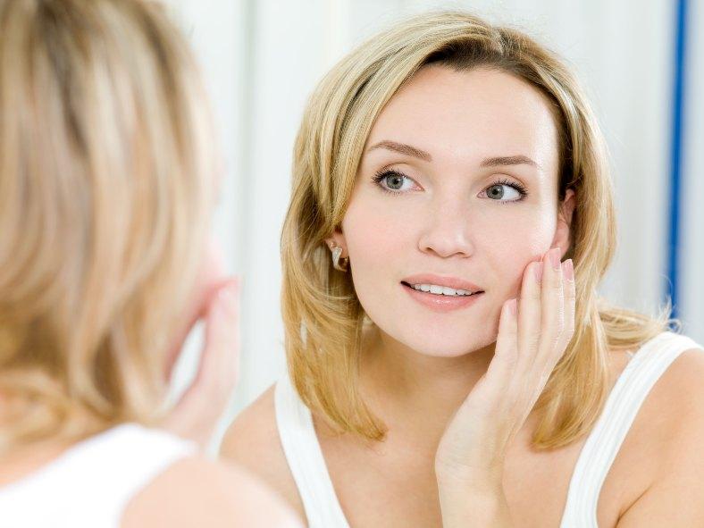 Chica en el espejo mirando su piel.