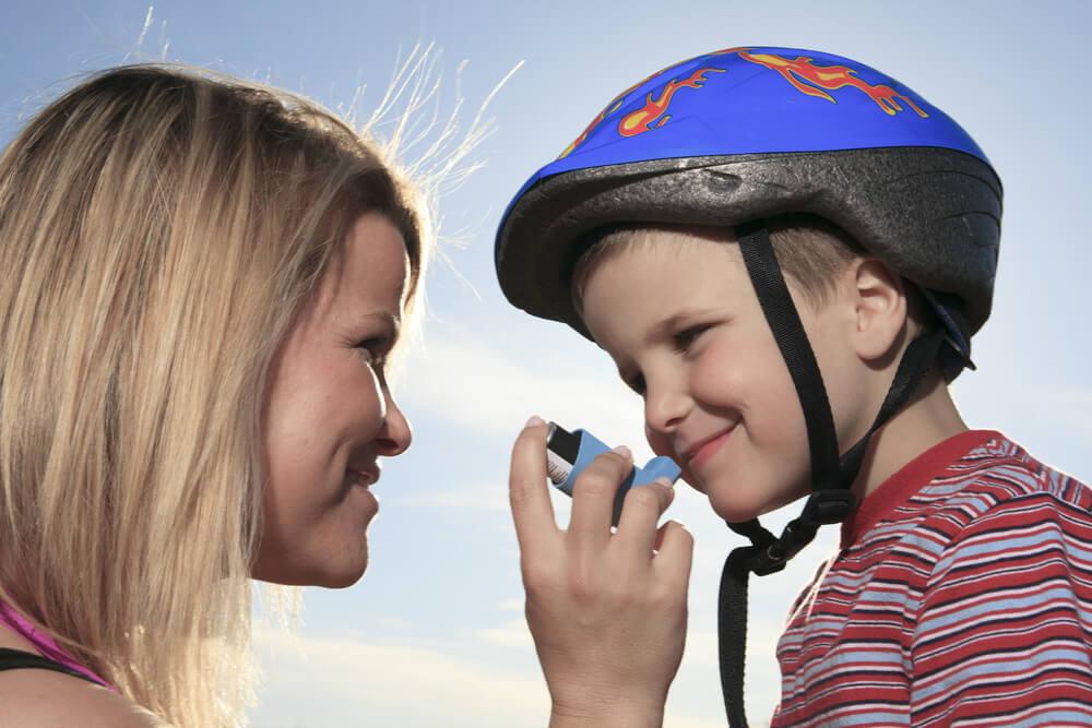 Madre ofrece inhalador a su hijo.